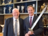 Charles Clarke and Dean Jack Knott pose with the Conan movie sword while attending a conversation hosted by the Schwarzenegger Institute.