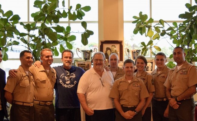 Governor Schwarzenegger and John Milius take a picture with leaders from the United States Marine Corps.